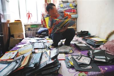"""4月19日,太原市小店区一出租屋内,两大蛇皮袋空包裹铺满张义的床铺。共计876件空包裹是张义经营快递网点时代收的""""刷单件""""。"""