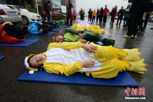 """资料图:世界睡眠日前夕,被誉为中国""""睡眠先生""""的唐堂带领众多市民来到长沙街头进行""""睡大街""""公益行为艺术展示。 杨华峰 摄"""