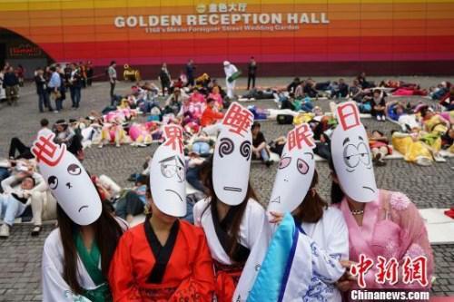 """資料圖:重慶某景區工作人員戴着""""世界睡眠日""""面具。 楊孝勇 攝"""