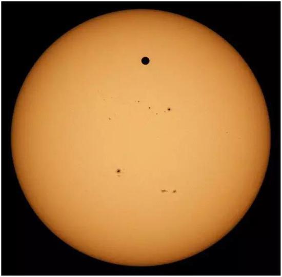 图2. 金星从太阳前方穿越,2012年拍摄于夏威夷哈雷安卡拉。金星是太阳圆面上黑色的圆点,其他不那么明显的特征是太阳黑子和太阳高能活动增强的区域。(由克莱中心天文台的罗恩·丹托魏特茨和威廉学院-霍普金斯天文台的杰伊·巴萨乔夫拍摄)