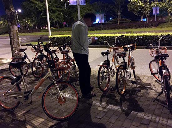 """已经骑着一辆单车的中年男子,正在寻找另一辆""""红包车""""。"""