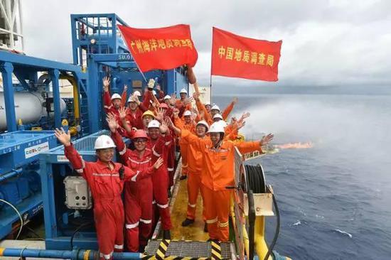 """在""""蓝鲸一号""""钻探平台上,工作人员庆祝天然气水合物试采成功(5月16日摄)。新华社记者梁旭摄"""