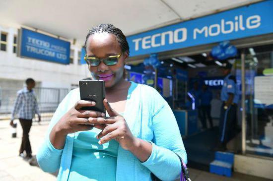 在肯尼亚首都内罗毕市中心,一名女子在一家传音手机专卖店前使用自己的传音手机。(新华社)