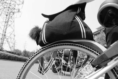 摩拜单车塑料材质的挡泥板较软,不足五公斤的书包将挡泥板压在车轮胎上摄/记者宫主