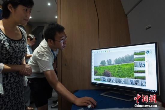 8月4日,高铁超高速无线通信(EUHT)技术在京津城际高铁列车上进行演示。经测试,由广东新岸线公司提供技术及系统集成的EUHT技术在时速300公里的高铁运行途中,通信切换可靠性达到100%,平均通信延时5ms,空口时延小于1ms,平均传输带宽达到150Mbps,超过目前世界最先进的第四代移动通信技术(4G)10倍以上,达到下一代(5G)技术提出的性能指标要求。图为工作人员实际演示经该技术向车内实时高质量回传的沿线摄像头拍摄的场景。中新社记者侯宇摄