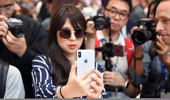 一位正在試用iPhone X的女記者。@視覺中國