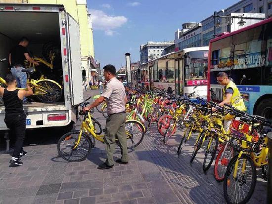 资料图:执法人员清理乱停乱放的共享单车