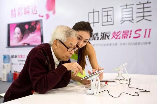 北京某展会上一位老人在酷派工作人员的指导下使用酷派手机。@视觉中国
