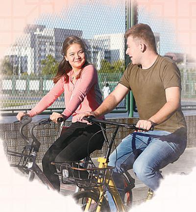 法国人张浩成(右)和哈萨克斯坦人奇娜拉在校园里骑共享单车。