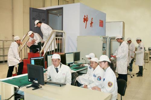 图为飞船组工作人员在调试空间交会对接的模拟设备。中国航天科技集团公司供图