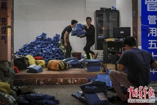 """11月5日晚11点,广东省广州市里仁洞村一个快递点里,工作人员杨雪丽在收发快递。里仁洞村是著名的""""淘宝村""""。记者 赵迪/摄"""