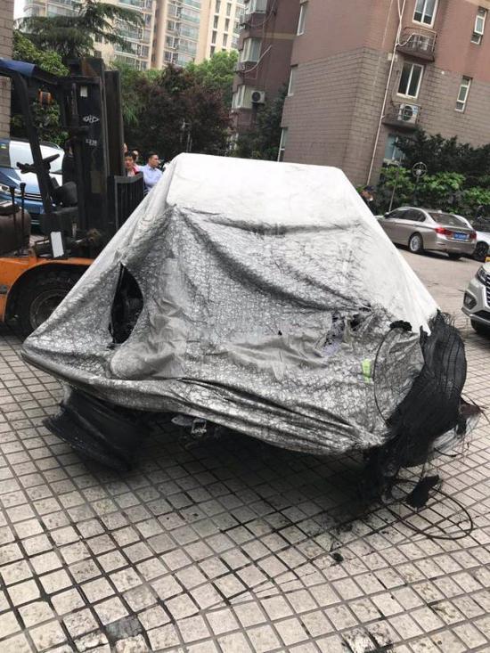 4月23日,被烧损的特斯拉轿车准备运离小区。 网友供图