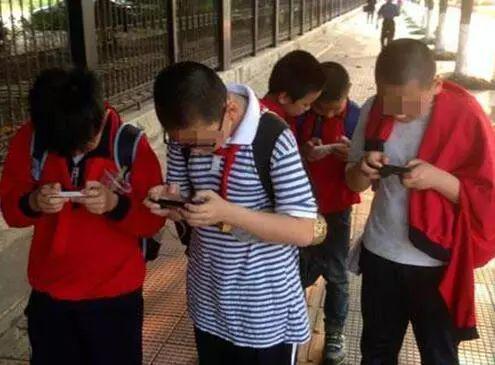 街头沉迷玩手机的小学生。