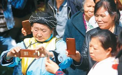 在贵州省毕节市大方县宣慰府,黄友先老人正在用智能手机拍视频,与大家分享沿途美景。  罗大富摄(人民图片)