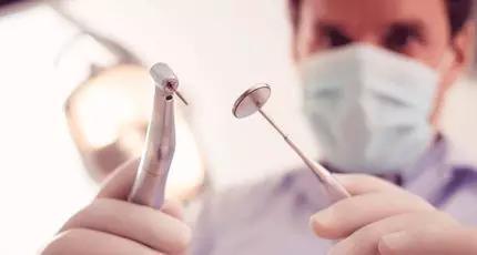 """研究者小心操作着医用牙钩和牙钻来治疗牙齿问题,从我们远古祖先那不那么洁白的牙齿上""""阅读""""着他们的健康史。DRAGONIMAGES/ISTOCKPHOTO"""