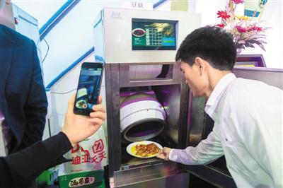 近日,一款商用智能自动炒菜机出现在上交会现场,现场工作人员使用该机器炒制了多款美食,吸引了观众品尝。   王 冈摄(人民图片)
