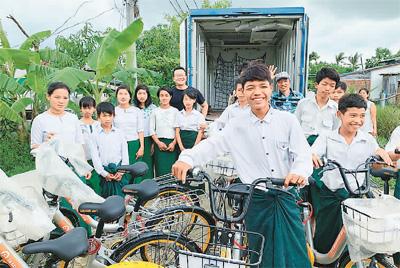 缅甸创业者迈克(左七)将废弃共享单车回收,捐赠给仰光的贫困学生。  (Lesswalk官网供图)