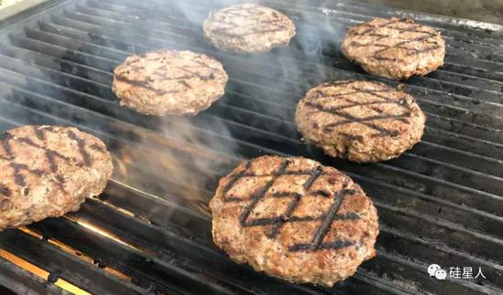 肉饼烤至全熟,厨师立刻把饼刷上千岛酱,夹进汉堡里。