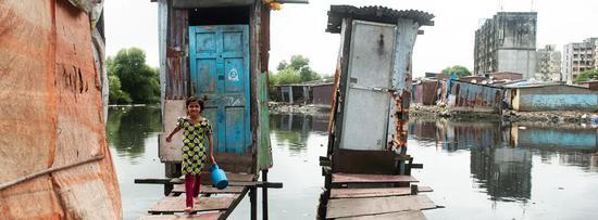 7岁的伊里亚姆?谢赫从水上厕所里出来,该厕所建于孟买拉菲克?纳加尔的一条排水沟上,由木桩支撑。图/联合国水机制