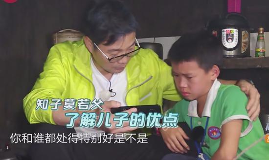 极限男人帮陪伴留守儿童,王迅正给孩子播放他爸爸的录像。/《极限挑战》第四季