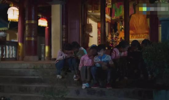 低头玩手机的孩子和他们背后沉默的佛祖。/电影《米花之味》
