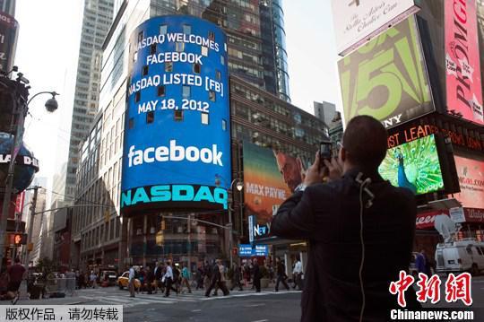 """資料圖片:2012年5月18日,行人從美國紐約納斯達克證券交易所外經過,電子顯示屏上顯示出""""臉書""""在納斯達克上市的消息。"""