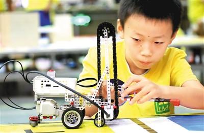 2017年8月13日,2017年青少年AI人工智能设计大赛在江苏苏州开赛,一名小选手进行赛前调试。王建中摄(新华社发)
