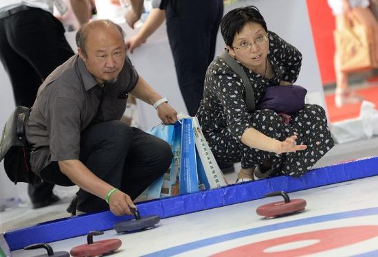 两位观众在2017陕西体育博览会上体验仿真冰壶。新华社记者李一博摄