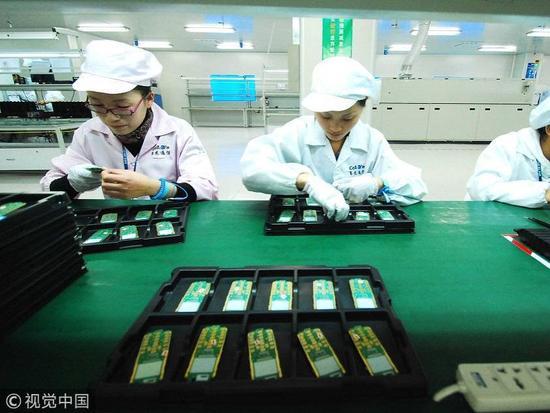 本文头图:2010年11月10日,江西省九江市共青城工业园区,赛龙通信公司的工作人员在进行手机芯片生产作业。