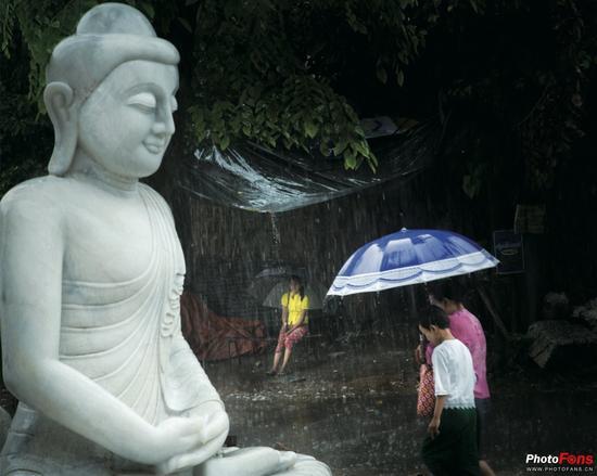 静置的佛像和雨中行走的行人,一动一静的画面氛围,颇有韵味。