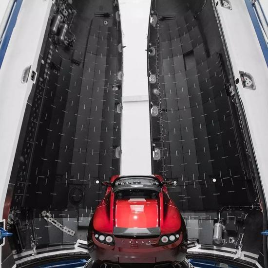 等待发射升空的特斯拉跑车,图片两侧是猎鹰重型火箭的整流罩