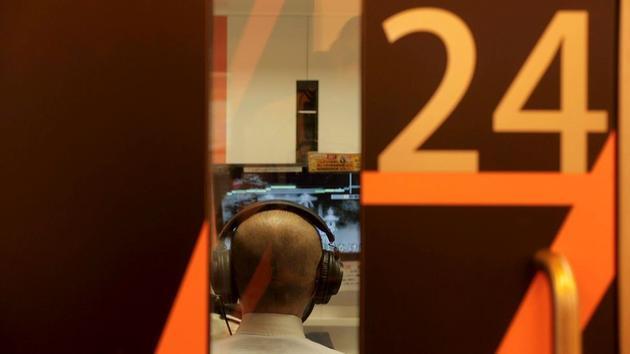 在日本新宿区的1Kara,顾客头戴耳机和麦克风,在电话亭大小的空间中独自唱歌。