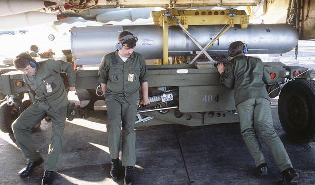 三位地勤人员正在将一颗Mark 28核弹从美国空军B-52H轰炸机卸下