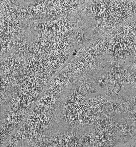 """这张图像上暗色的块体可能是一块""""脏""""冰块""""漂浮""""在密度更大的固态氮冰表面之上,它已经逐渐接近循环边缘的裂隙区域。"""