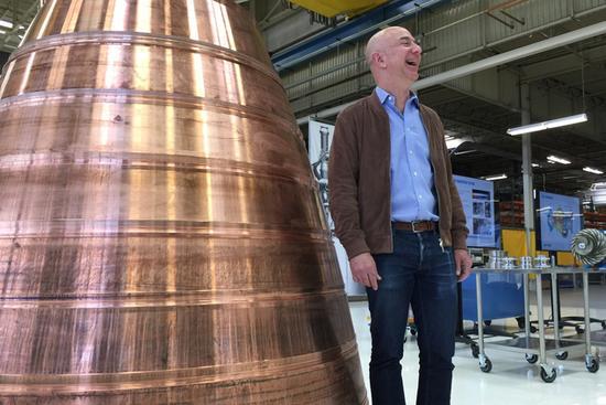 图为亚马逊创始人杰夫?贝佐斯在带领媒体参观Blue Origin公司时,站在一台装在火箭引擎上的铜排气喷管边上。这是该公司首次向媒体敞开大门,让他们一瞥Blue Origin公司研发下一代火箭的过程。
