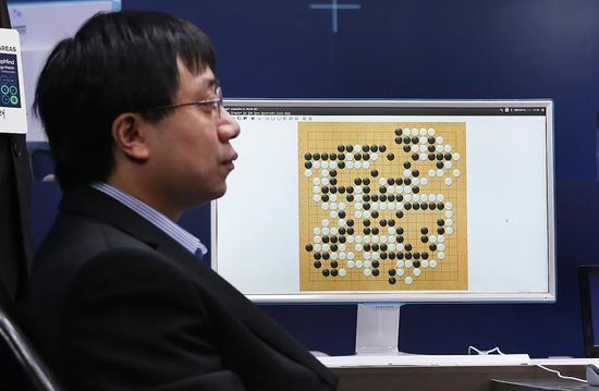 图注:代替AlphaGo执子的黄士杰冷静得像是工厂里的操作员