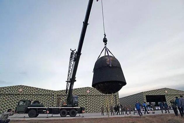 经过12天太空飞行之后返回地面的实践十号返回舱,被科研人员翻转吊起。图片来源:本文作者