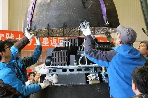 """科研人员打开实践十号卫星回收舱的""""头壳"""",露出了里面的实验装置。图片来源:本文作者"""