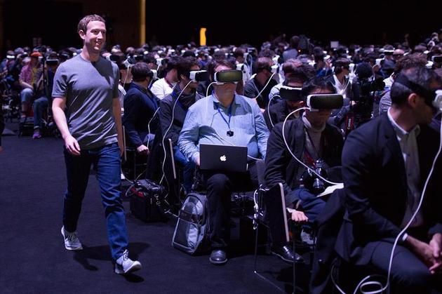 2016年三星在西班牙巴塞罗那召开的新品发布会上,Facebook创始人兼CEO马克·扎克伯格走过正在体验三星VR产品的观众,准备上台演讲。