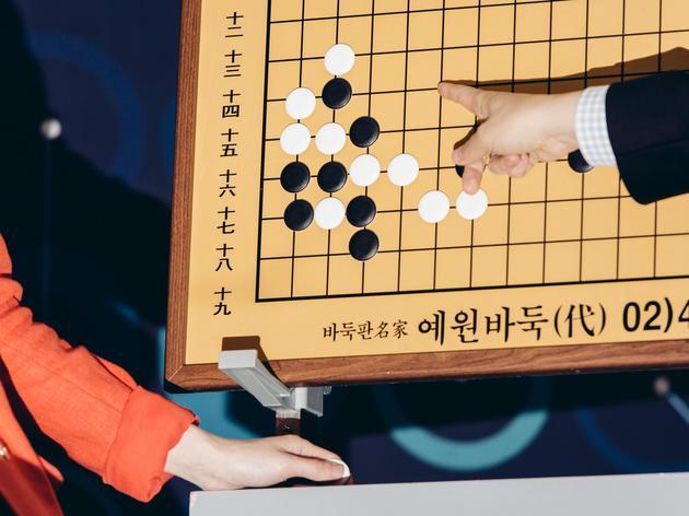 围棋讲解员在赛后发布会上分析棋局。