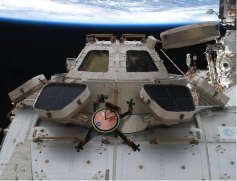 在这幅展现美国宇航局技术的艺术家幻想图中,受壁虎启发而发明的LEMUR机器人正紧贴在空间站的外壁上。图片来源:美国宇航局/ JPL-CALTECH