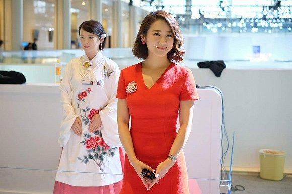 """人形机器人""""佳佳""""(左)与双语主持人、艾问传媒创始人艾诚(右)"""