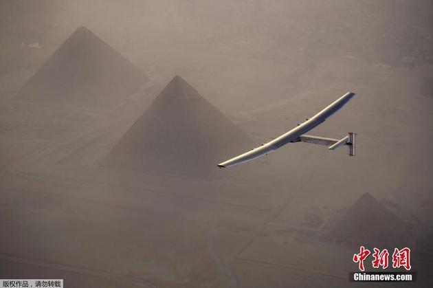 """当地时间7月13日,瑞士飞行员驾驶的全球最大太阳能飞机""""阳光动力2号""""从埃及吉萨金字塔上空飞过,之后飞机在开罗国际机场降落。"""