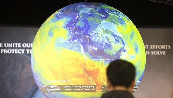 2015年巴黎气候峰会期间人们看着地球的图片。来源:AFP
