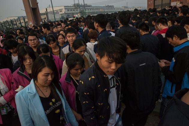 郑州富士康工厂,晚班工人离厂,早班工人进厂。这家工厂每天可生产50万部iPhone。