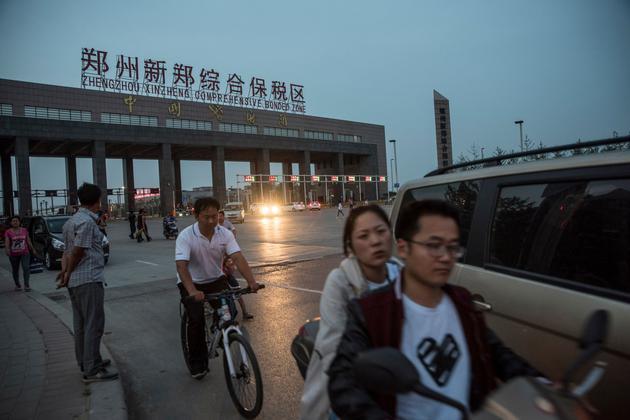 结束一天的工作,富士康的工人骑车穿过保税区的大门。