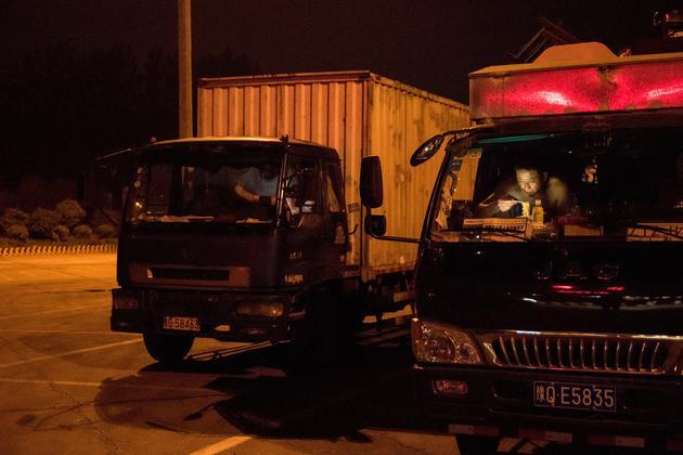 郑州与上海间的一个高速公路服务区,卡车司机正在吃晚饭。没有任何特殊标记的卡车将iPhone运到中国各地。