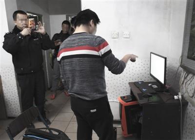 """2016年12月30日,昌平沙河线材厂东宿舍居民区,犯罪嫌疑人陈某家,陈某指着自己的电脑,办案民警拍照取证。陈某,涉嫌通过网络向900多人出售""""裸条""""的淫秽图片及视频,获利数万元,被北京警方抓获。新京报记者 尹亚飞 摄"""