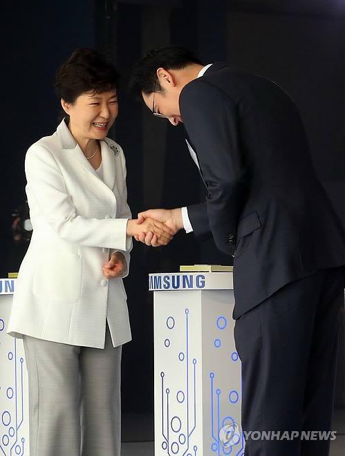 2015年,三星半导体工厂开工仪式上,朴槿惠(左)与李在镕握手。