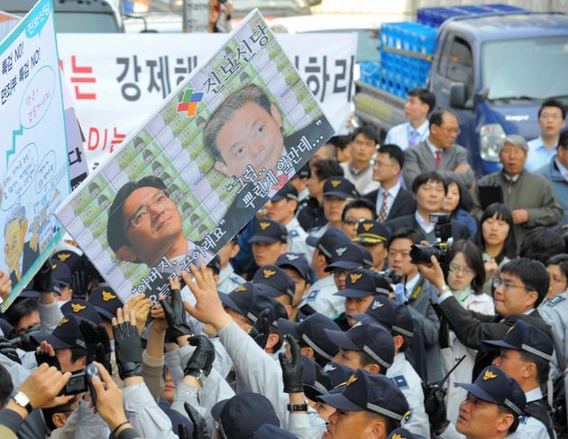 抗议者高举李家父子肖像
